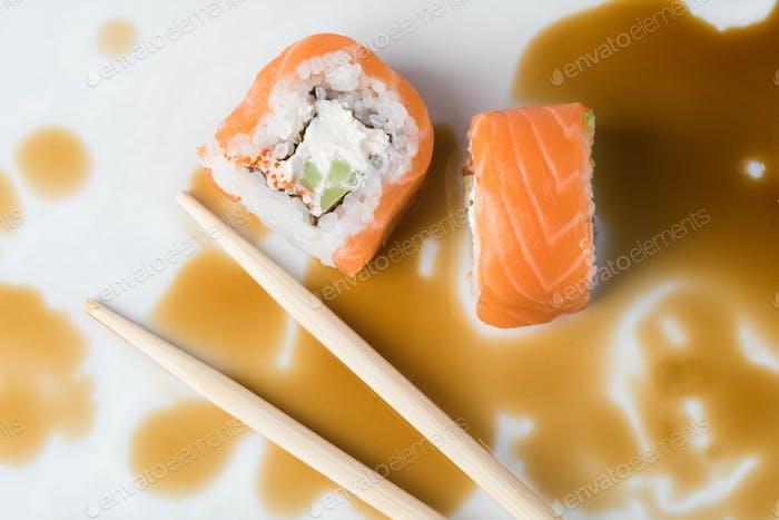 Sushi roll in chopsticks in soy sauce, closeup