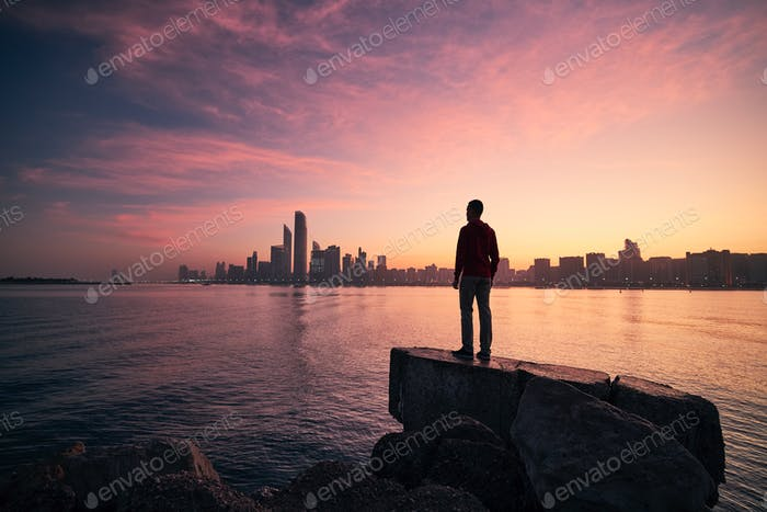 Man looking on cityscape at colorful dawn