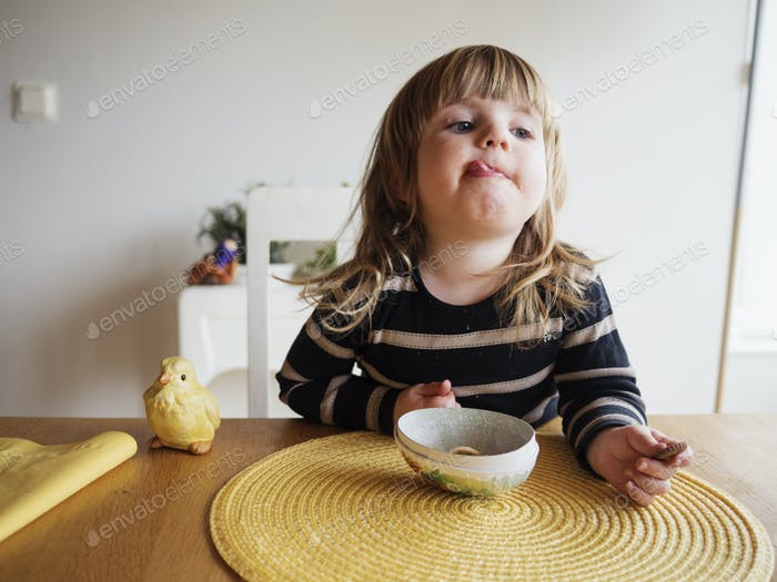 Little girl sticking out tongue at dining table