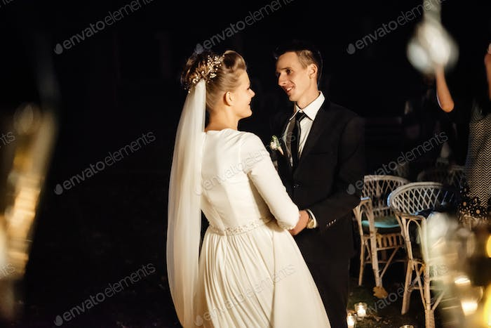 gorgeous bride and stylish groom at evening wedding ceremony