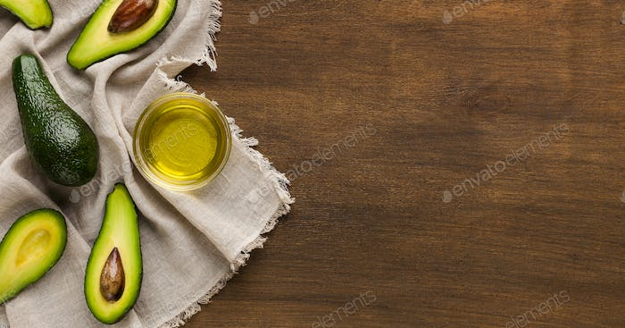 Sliced and whole avocadoes and bowl of oil on table