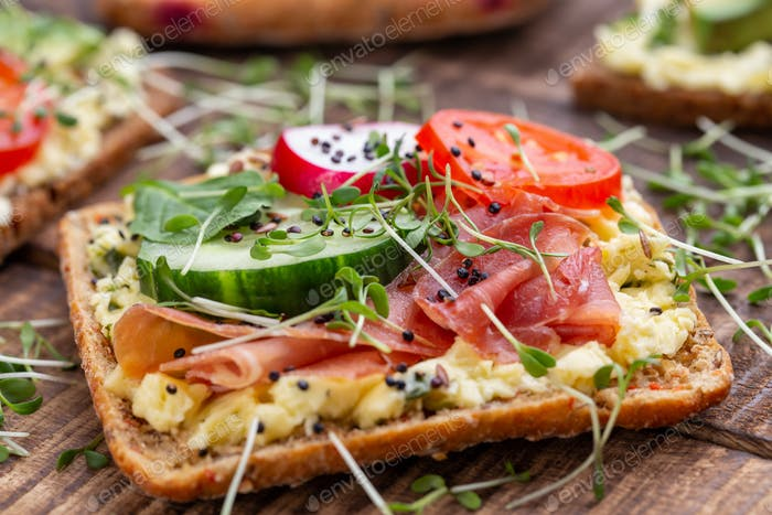 Sandwiches with cream cheese, vegetables and salami.