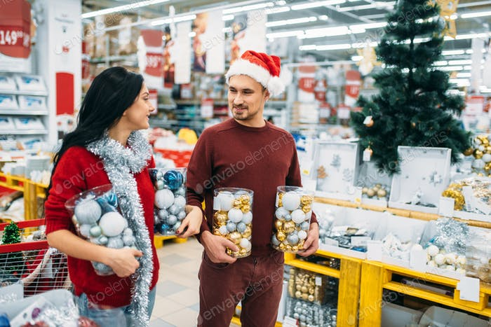 Young couple with boxes full of Christmas balls