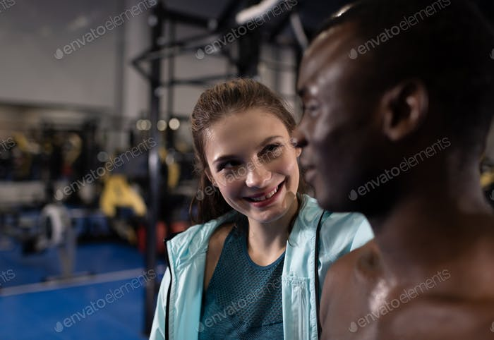 Cheerful woman joking with boyfriend in fitness center