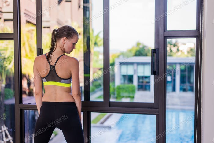 Back view of young woman stretching doing morning workout at luxury hotel resort with a great view
