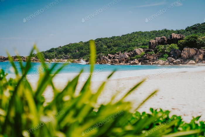 Grand Anse beach at La Digue island, Seychelles. Famous granite rock formations framed in defocused