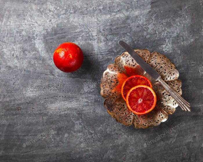 Blood Orange in a metal Plate with a knife