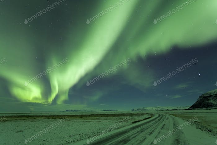 Nightsky with green Northern Lights, Aurora Borealis over winter landscape.