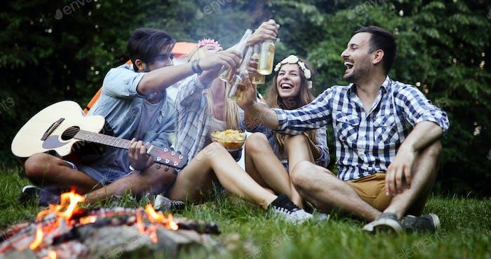 Friends enjoying music near campfire