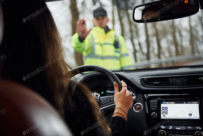 Male police officer in green uniform stops vehicle with female driver on the road