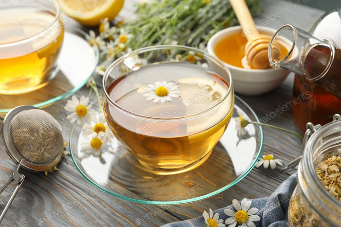 Composition with chamomile tea on gray wooden background