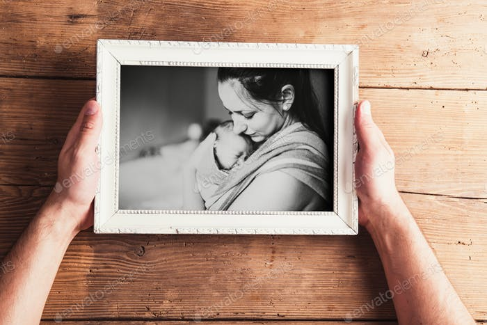 Mothers day composition. Picture frame. Wooden background. Studio shot.