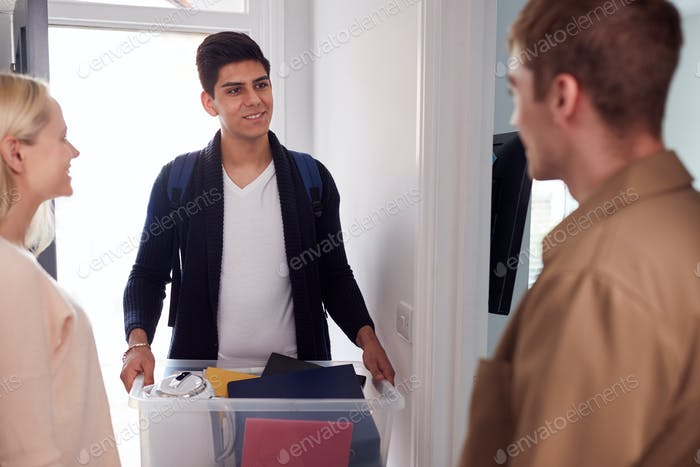 Male College Student Carrying Box Moving Into Accommodation Meeting House Mates