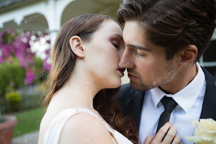 Close up of newlywed couple kissing at park