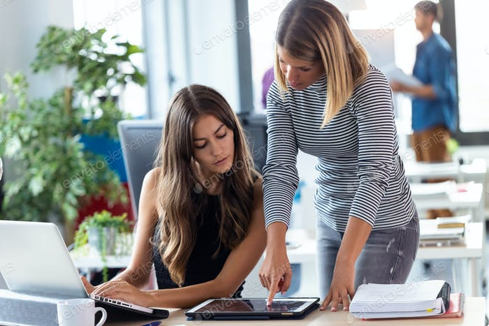 Two business young women working together with digital tablet in the modern startup office.