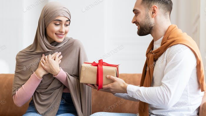 Arab Man Surprising Wife Giving Wrapped Present Box At Home