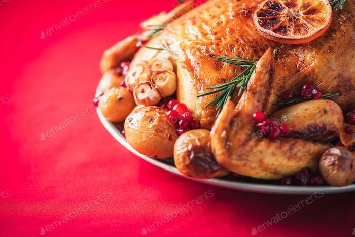 Gebratenes Huhn mit Orangen, Rosmarin und Preiselbeeren auf Teller über rotem Hintergrund. Traditionelle
