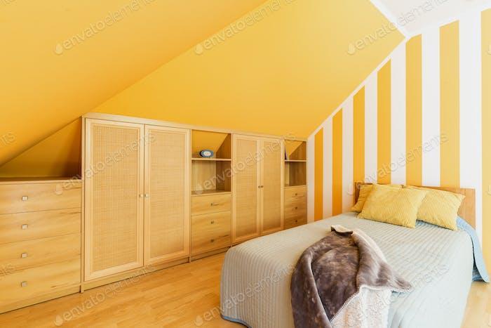 Dachgeschoss Schlafzimmer mit intensiven gelben Wänden
