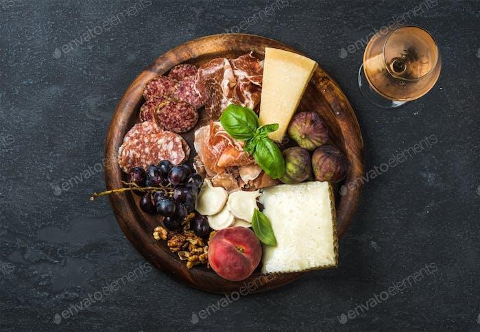 Italian antipasti snacks and glass of rose wine