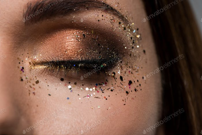 cropped shot of woman with golden gloss around closed eye as fashion makeup