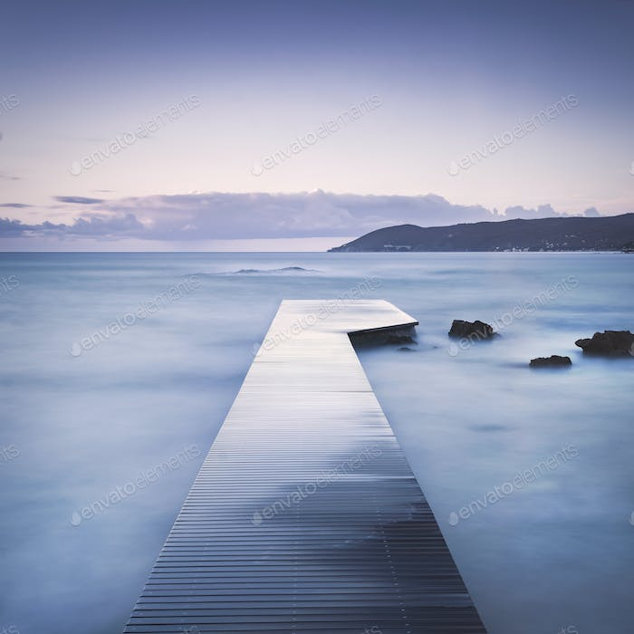 Wooden pier, rocks and sea on misty sunset.