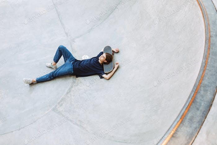 Young guy dreamily lying on skateboard in empty bowl at skatepar