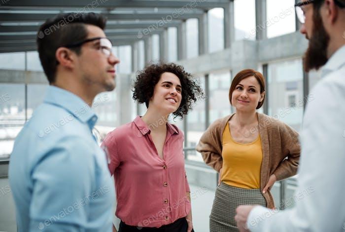 Eine Gruppe junger Geschäftsleute, die im Amt stehen und reden.