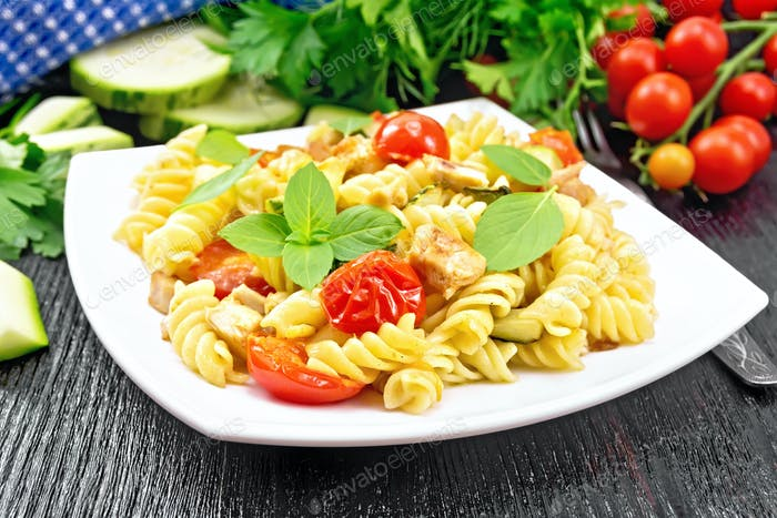 Fusilli with chicken and tomatoes in plate on black wooden board