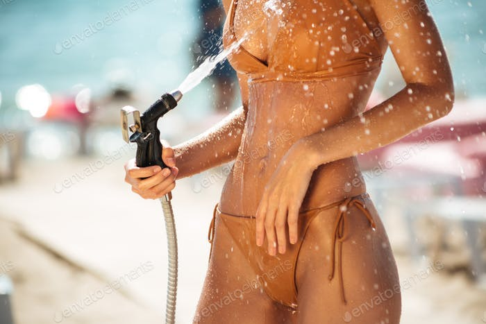 Young woman body rinsing beach sand off on beach