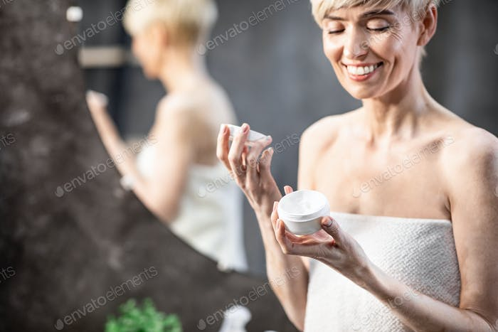 Smiling Woman Opening Facial Cream Standing In Bathroom At Home
