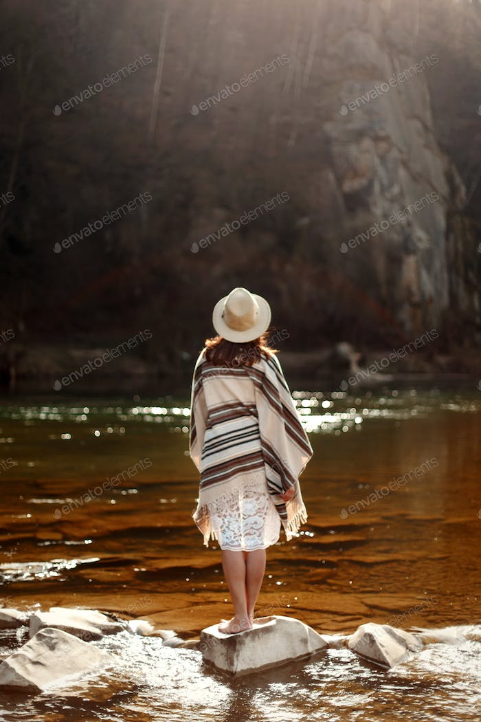 beautiful woman traveler back standing on rocks in river, wearing hat and poncho