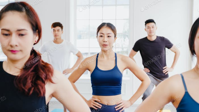 Asian attractive people practicing yoga lesson with instructor. Asia group of women exercising.