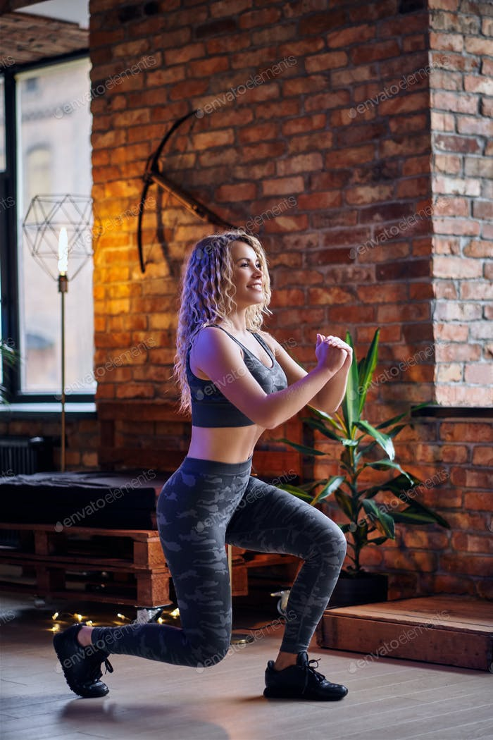 Blond sporty female doing workout in a room with loft interior.