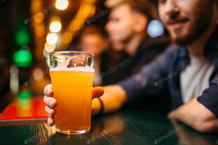 Male person holds glass with beer at bar counter