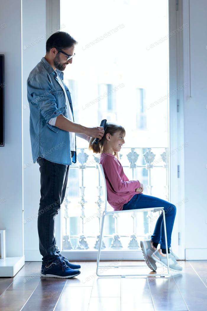 Handsome young father making a ponytail to his daughter while she sitting on a chair at home.