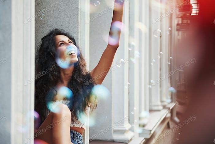 La vida en colores. Hermosa mujer con cabello negro rizado tener buen tiempo en la ciudad durante el día