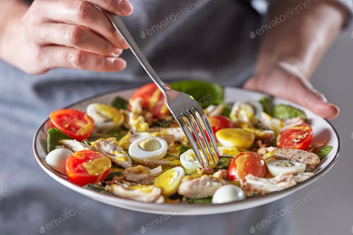Female hands hold the plate with healthy freshly cooked salad and fork on a gray background