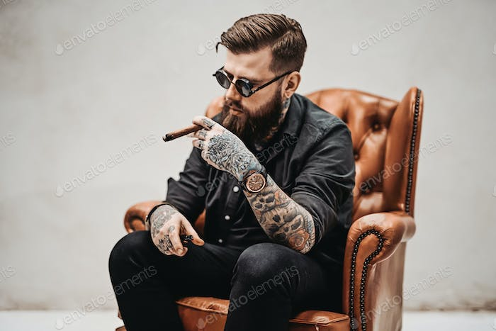 Bearded tattooed man with stylish haircut in sunglasses who smokes a cigar
