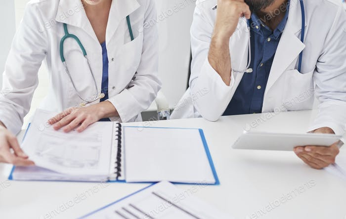 Two busy doctors checking medical results