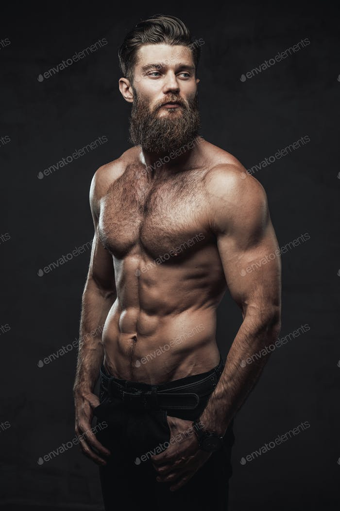 Naked and muscular guy posing in dark background