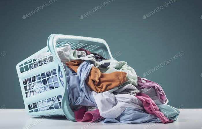 Heap of dirty clothes and laundry basket