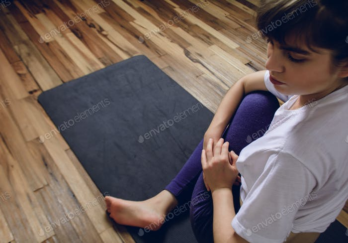 Young woman practicing yoga in home.