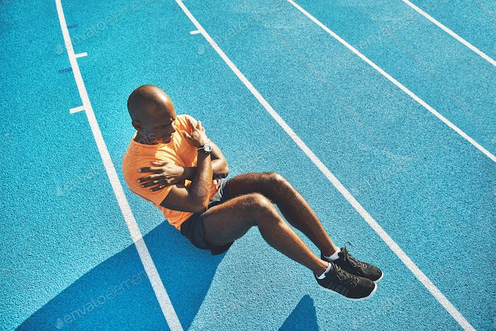Fit and focused young athlete doing crunches on a track