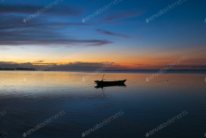 Sunset with fisher boat and still water on Gili Air Island, Indo