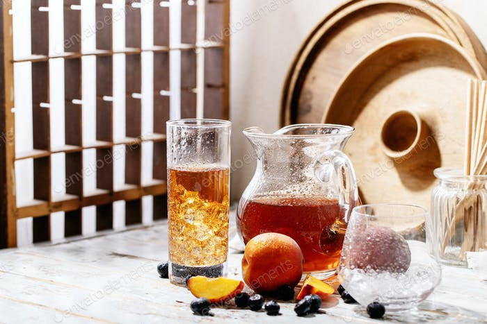 Cup of peach ice tea served with fresh peach