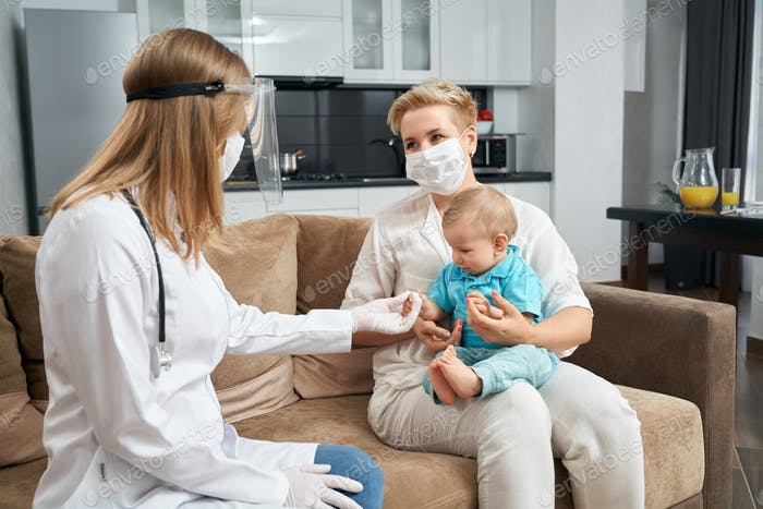 Competent doctor in mask examining baby at home