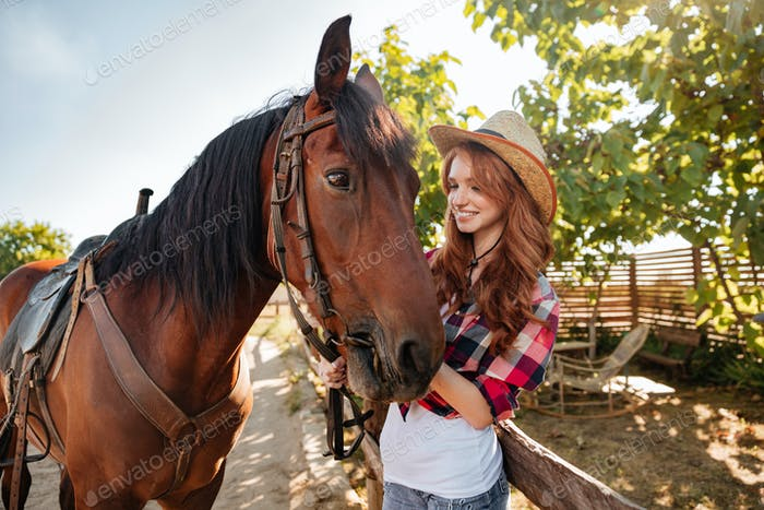 Happy woman cowgirl taking care of her horse on farm