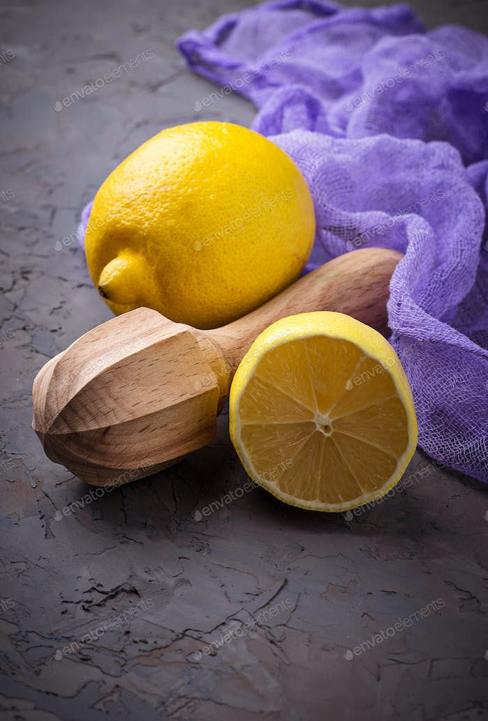 Fresh lemon and juicer on concrete background