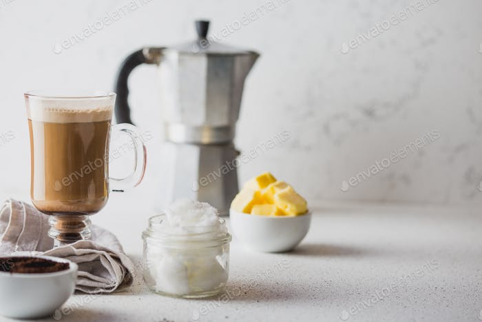 Cup of bulletproof coffee and ingredients on white background. Copy space.
