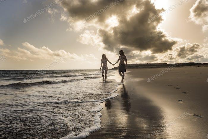 romantischer Sonnenuntergang am Strand mit kaukasischen schönen jungen Paaren am Ufer